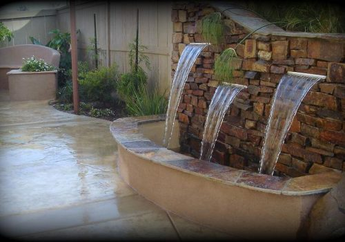 beautiful brick fountain with stamped concrete patio
